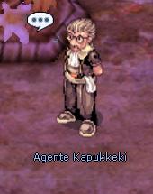 personagem Agente Kapukkeki, vestido com um traje nobre marrom e com um tecido branco amarrado na cintura. Ao fundo, um terreno arroxeado. Acima do personagem, um balão de diálogo com reticências dentro.